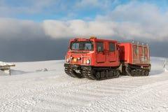 在冬天山的红色ratrak snowcat 用雪报道的一红色雪tucker 库存照片