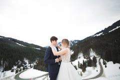 在冬天山的美好的年轻夫妇 恋人冬天步行  拥抱人妇女 免版税库存照片