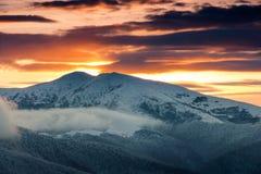 在冬天山的美好的日出 剧烈的多云结束天空 免版税库存照片
