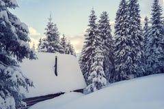 在冬天山的老木客舱 免版税库存照片