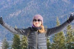 在冬天山背景的女孩 愉快美丽快乐 免版税库存图片