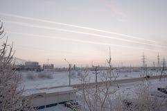 在冬天工业街道上的桃红色日落有在天空的印刷品的在从窗口的飞机视图以后在冷的冷淡的晚上 免版税库存照片