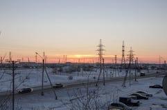 在冬天工业街道上的橙色日落 从窗口的看法在冷淡的晚上 免版税库存照片