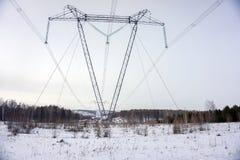 在冬天支持在一个树木繁茂区的顶上的输电线 库存照片