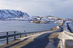 在冬天日落的著名fredvang桥梁与在backgrond的山和在前景的美好的阴影线, lofoten海岛,不 免版税图库摄影