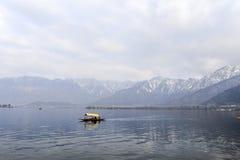 在冬天期间,与一条小船的一个美好的风景在Dal湖克什米尔,印度 库存照片