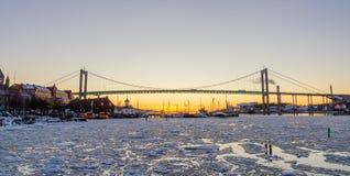 在冬天期间,哥特人-在冻Gota河的美好的日落有Hisingsleden桥梁的在港口区 库存图片
