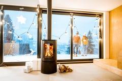 在冬天期间,有壁炉的在大阳台的议院和夫妇 库存图片