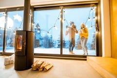 在冬天期间,有壁炉的在大阳台的议院和夫妇 免版税库存图片