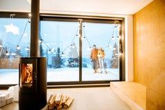 在冬天期间,有壁炉的在大阳台的议院和夫妇 免版税图库摄影