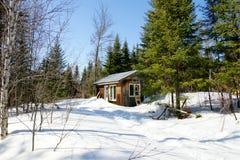 在冬天期间的老木客舱 免版税库存图片