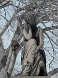 在冬天期间,一个老坟园雕象 库存图片