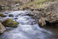 在冬天期间,一条小小河的急流长的曝光  免版税库存照片