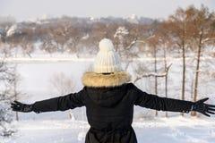 在冬天期间,女孩投掷在空气的雪 免版税图库摄影
