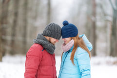 在冬天木头的年轻夫妇 他们的眼睛掩藏在盖帽下 库存照片