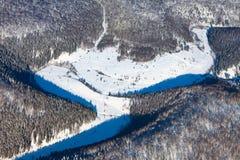 在冬天树木繁茂的小山的斯诺伊峡谷,顶视图 库存图片