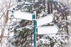 在冬天森林背景的箭头牌 免版税库存图片