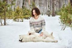 在冬天森林里走与狗的女孩 雪落 免版税库存照片