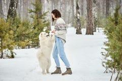 在冬天森林里走与狗的女孩 雪落 库存照片