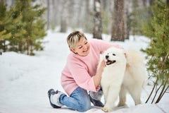 在冬天森林里走与狗的妇女 雪落 免版税库存照片