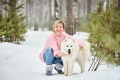 在冬天森林里走与狗的妇女 雪落 免版税图库摄影