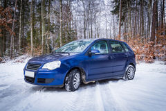 在冬天森林风景的蓝色汽车 库存图片