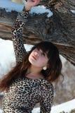 在冬天橡木附近的美丽的少妇 免版税库存照片