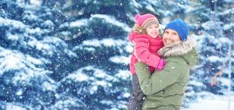在冬天步行的愉快的家庭 爸爸和儿童女婴 免版税库存照片