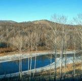在冬天河在小山和冻银行中流动 免版税库存照片