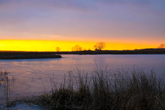 在冬天河的日落 库存照片