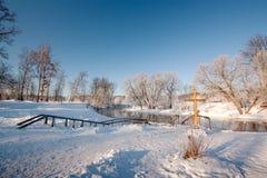 在冬天河的海岸的基督徒十字架 库存照片