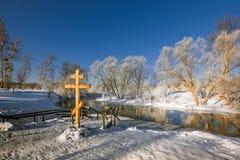 在冬天河的海岸的基督徒十字架 免版税库存图片