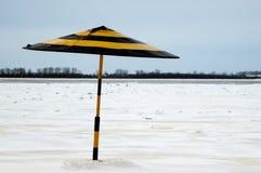 在冬天海滩的一把偏重伞 免版税库存照片