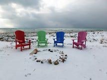 在冬天海滩的四把五颜六色的椅子 库存照片