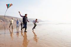 在冬天海滩的多一代家庭飞行风筝 图库摄影