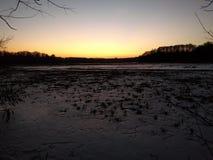 在冬天湖的黄昏 免版税库存照片