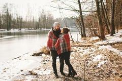 在冬天湖附近结合看在格子花呢披肩下 免版税库存照片