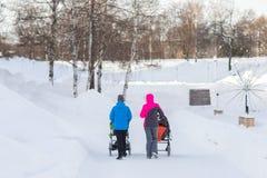 在冬天照顾走与一辆婴儿推车 库存照片