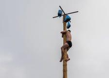 在冬天狂欢节Maslenitsa期间,供以人员攀登奖的杆 免版税库存图片