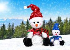 在冬天的圣诞老人帽子的两snowmens 库存图片