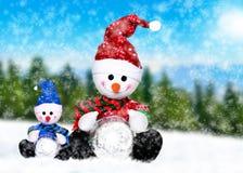 在冬天的圣诞老人帽子的两snowmens 免版税库存照片