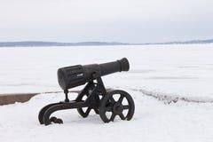 在冬天积雪的堤防的老大炮 免版税库存照片