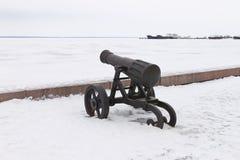 在冬天积雪的堤防的老生铁大炮 库存照片