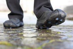 在冬天穿上鞋子钉的雪链子一条冰冷的路 库存图片
