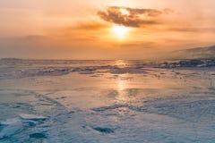 在冬天结冰的水湖的日落 库存照片