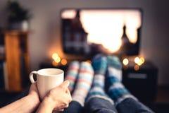 在冬天结合饮用的茶、巧克力热饮、蛋黄乳或者加香料的热葡萄酒和看着电视在温暖的舒适羊毛袜子 库存图片