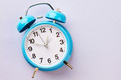 在冬天背景的蓝色减速火箭的闹钟 免版税库存图片