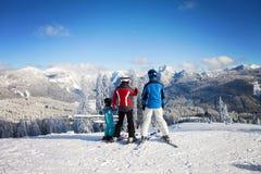 在冬天衣物的愉快的家庭在滑雪胜地 库存照片