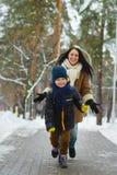 在冬天衣物的愉快的家庭 远离室外他的母亲的微笑的儿子奔跑 免版税库存图片