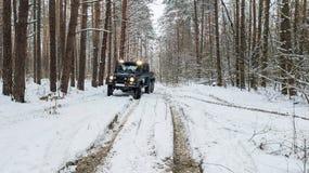 在冬天路之前乘坐在积雪的森林里的SUV 6x6的看法 库存图片